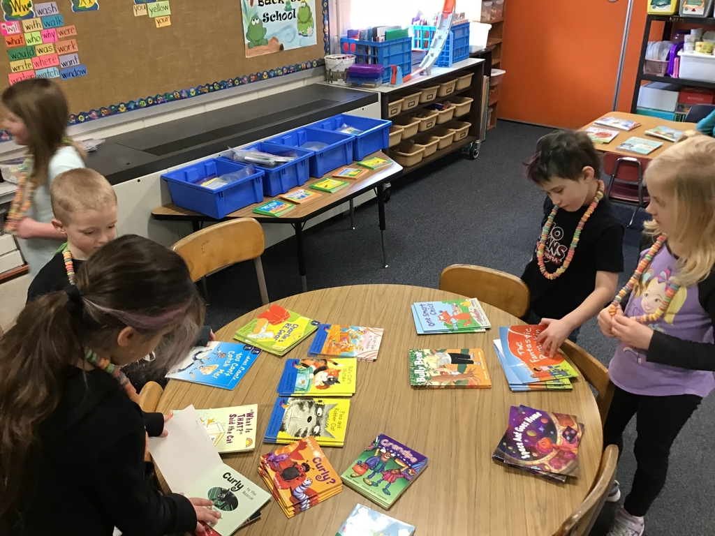First graders reading 100 books on the 100th day of school while wearing 100 fruit loop necklaces